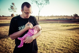Baby Aria's dad John comforts her at the end of a photoshoot on the outskirts of Kalgoorlie.